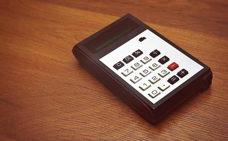 Ein alter Taschenrechner liegt auf einem antiken Tisch.